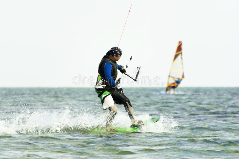 Kitesurfing and windsurfing action photos. Man rides a kite on windsurfer background. Selected focus. Kitesurfing Kiteboarding action photos man among waves royalty free stock photos