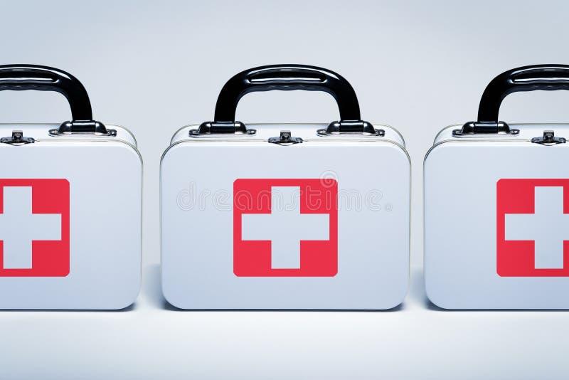 Kits de premiers secours dans une rangée sur le fond gris-clair images stock