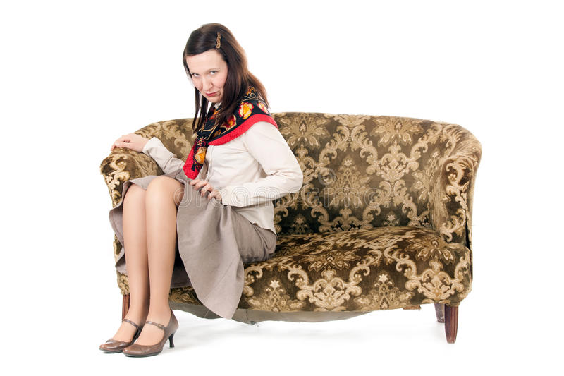 Kitsch woman enticing. Kitsch mature woman enticing on old fashioned sofa royalty free stock photography