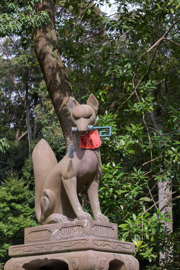 Kitsune, la volpe, tiene un digitare la sua bocca a Fushimi Inari Tais immagini stock libere da diritti