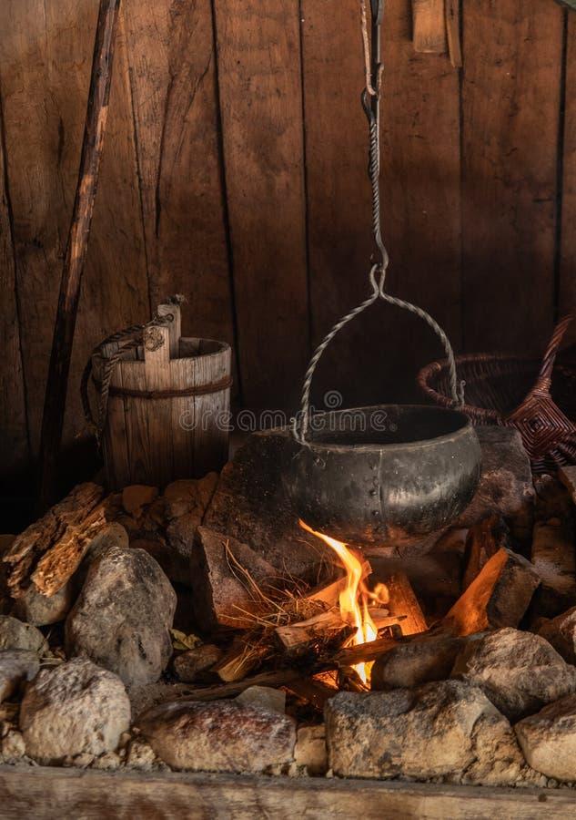 Kittel som lagar mat över en öppen brand i kabinen arkivbild
