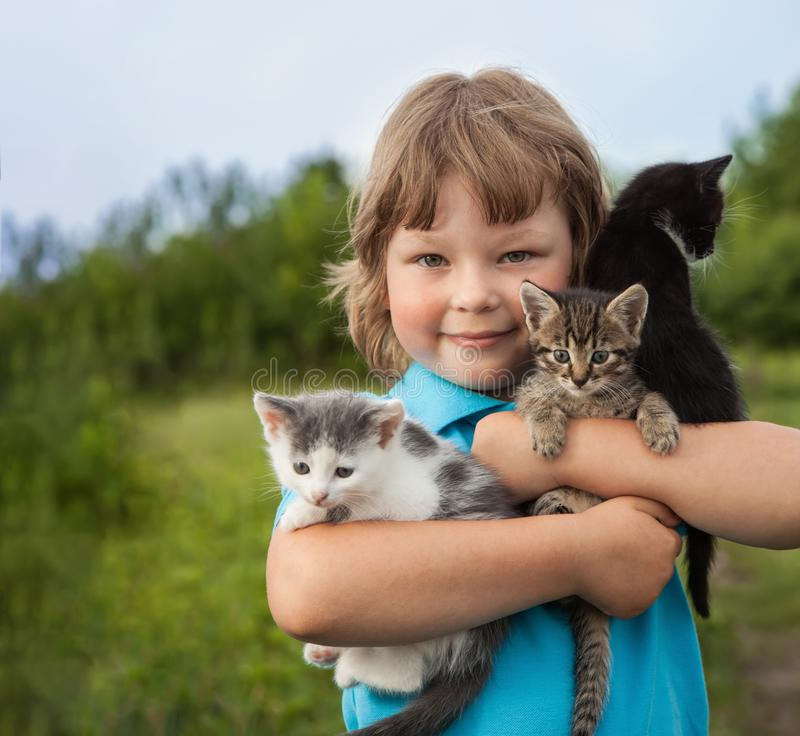 Kitten on arm of the boy outdoors, child huge his love pet. Kitten on the arm of the boy outdoors, child huge his love pet royalty free stock photography