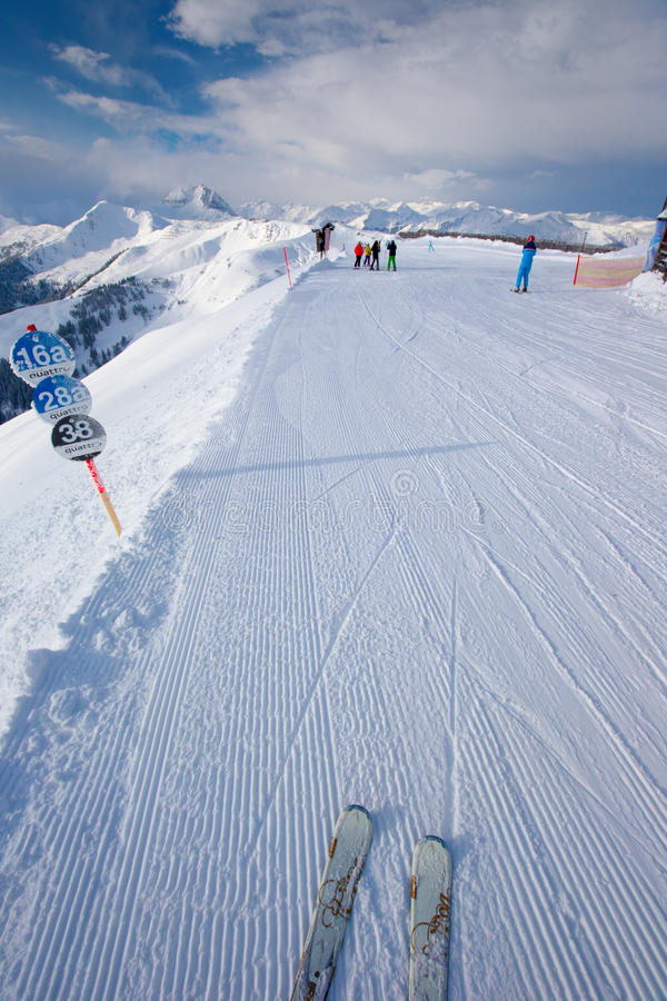 KITZBUEHEL, AUSTRIA - February 17, 2016 - Skiers skiing in Kitzbuehel ski resort and enjoying Alps view from the top stock image