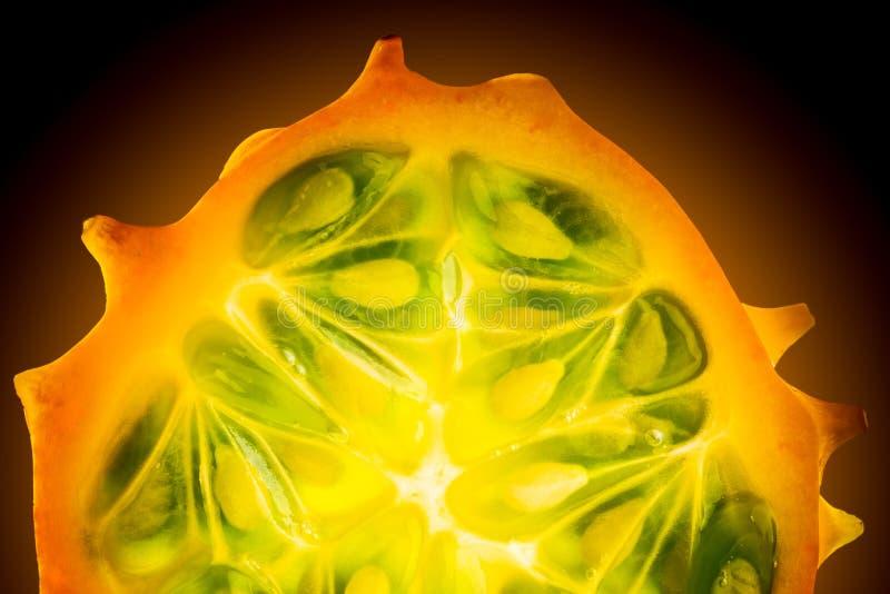 Kiwano oder gehörntes Melone Cucumis metuliferus schnitten zur Hälfte auf schwarzem Hintergrund lizenzfreies stockfoto