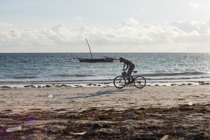 2018.02.21, Kiwengwa, Tanzania. Cyclist on the beach tonight. Travel around Zanzibar. Seascape of an african coast royalty free stock images