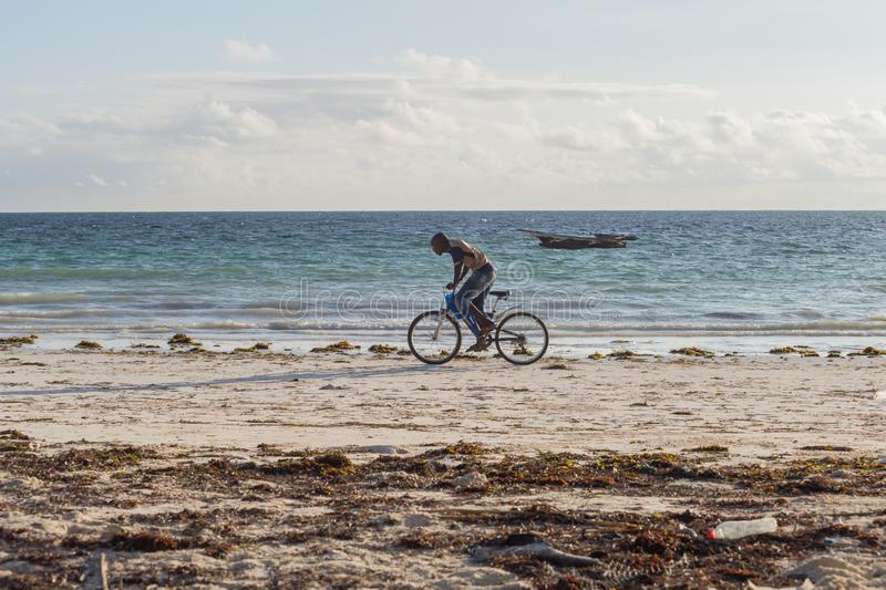 2018.02.21, Kiwengwa, Tanzania. Cyclist on the beach tonight. Travel around Zanzibar. Seascape of an african coast royalty free stock image