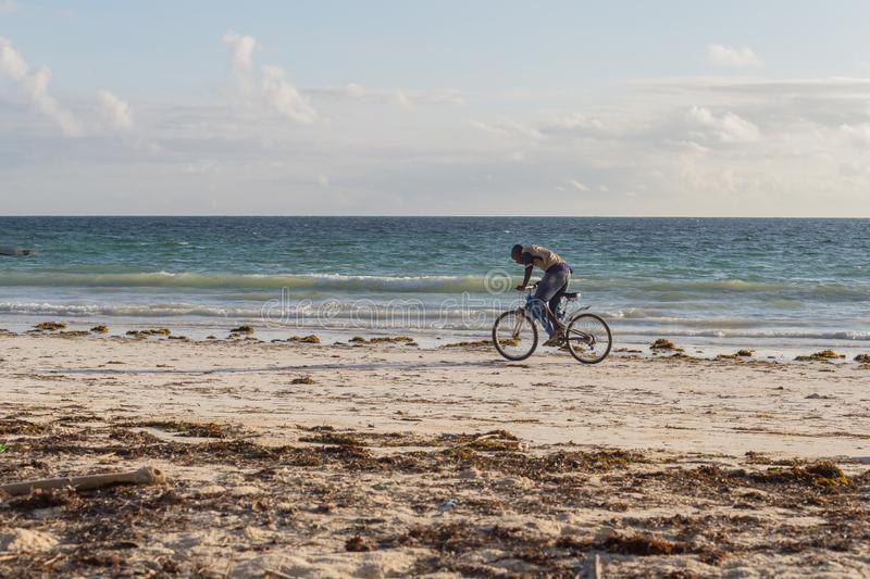 2018.02.21, Kiwengwa, Tanzania. Cyclist on the beach tonight. Travel around Zanzibar. Seascape of an african coast stock photo
