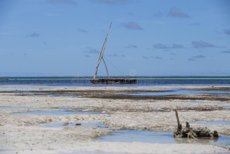 An old boat on the coastline on background of horizon line. 2018.02.21, Kiwengwa, Tanzania. An old boat on the coastline on background of horizon line. Travel royalty free stock photo