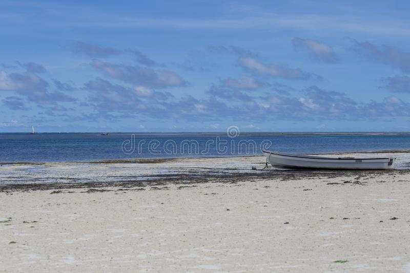 An old boat on the coastline on background of horizon line. 2018.02.21, Kiwengwa, Tanzania. An old boat on the coastline on background of horizon line. Travel royalty free stock images