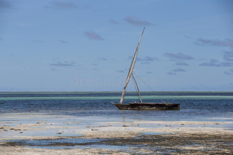 An old boat on the coastline on background of horizon line. 2018.02.21, Kiwengwa, Tanzania. An old boat on the coastline on background of horizon line. Travel royalty free stock photos