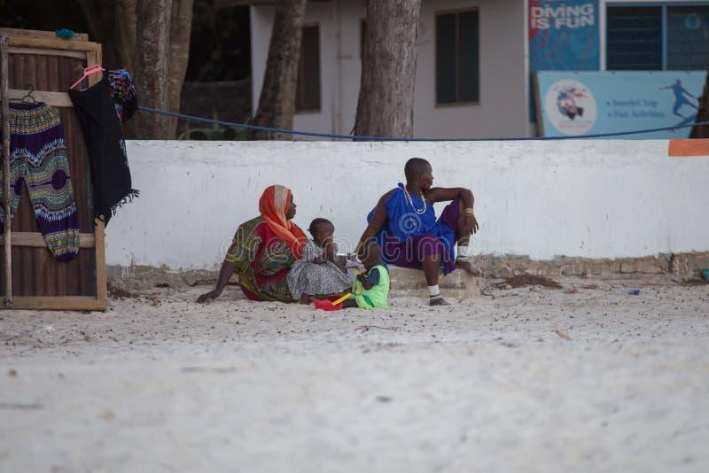 Ethnic people sitting on the beach. Tourism of Africa. 2018.02.21, Kiwengwa, Tanzania. Travel around Tanzania. People on the beach. Ethnic people sitting on the stock photography