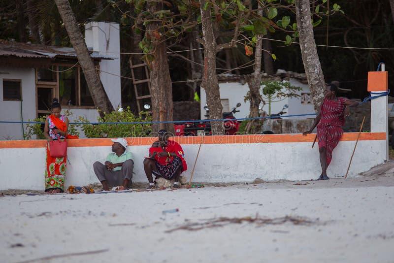 Ethnic people sitting on the beach. Tourism of Africa. 2018.02.21, Kiwengwa, Tanzania. Travel around Tanzania. People on the beach. Ethnic people sitting on the stock photo