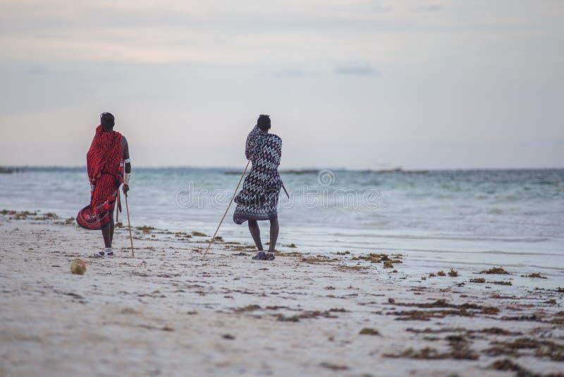 Two ethnic men standing on background of ocean. People on the beach. 2018.02.21, Kiwengwa, Tanzania. Travel around Tanzania. Two ethnic men standing on stock image