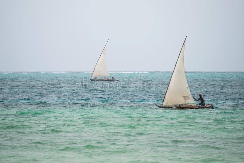 Fishermen sailing on dhows, Kiwengwa village, Zanzibar. KIWENGWA, ZANZIBAR - DEC 29, 2017: Fishermen sailing on traditional wooden boats in the Indian ocean near stock image