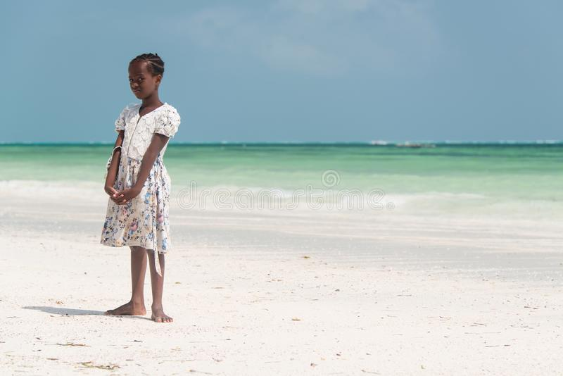 Kid posing on the beach at Kiwengwa village, Zanzibar. KIWENGWA, ZANZIBAR - DEC 26, 2017: young local girl posing on the beach at Kiwengwa village, Zanzibar stock image
