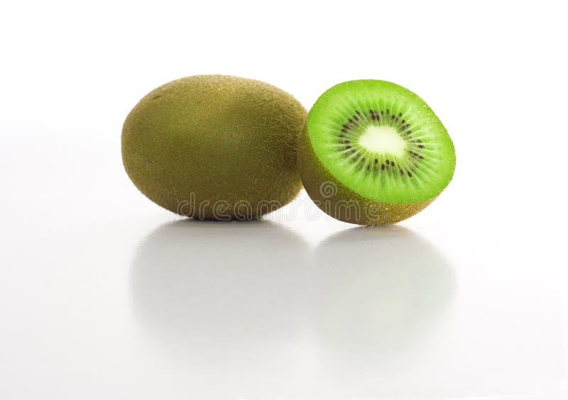 Kiwi. Isolated sliced kiwi fruit reflecting on white glossy surface stock photography