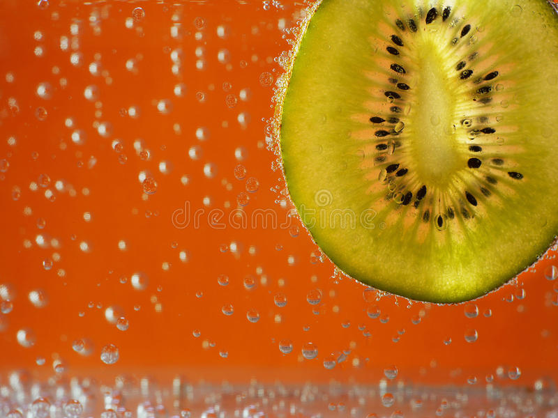 Kiwi in aerated water on background. Kiwi in aerated water on orange background stock photo