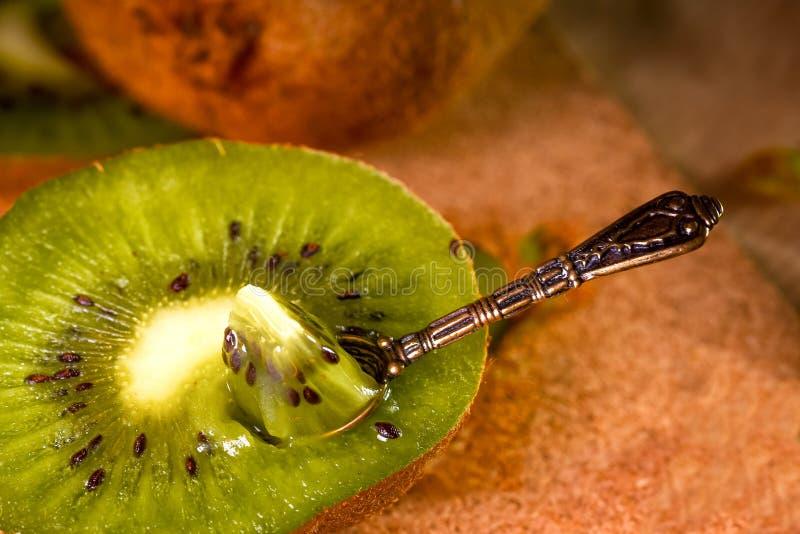 Kiwi avec une petite cuillère à l'intérieur Le concept de la consommation saine, detox Mangez photos libres de droits