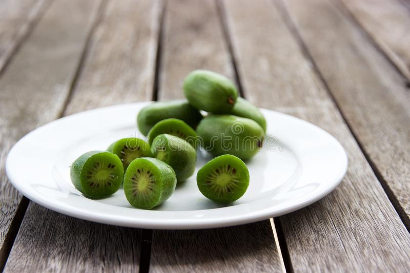 Kiwi berries (arctic kiwifruit) on white plate on wooden table. Sliced and whole kiwi berries presented on a white plate on a wooden slat table. Kiwi berries ( royalty free stock image