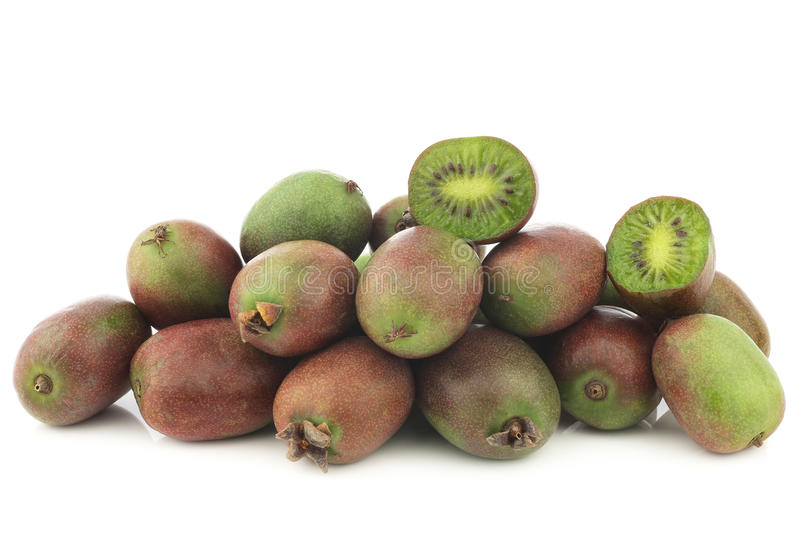 Kiwi berries and a cut one. On a white backgroun stock photos