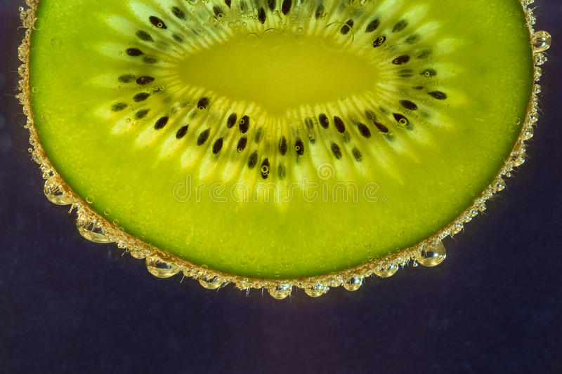 Kiwi with bubbles. Green kiwi with bubbles floating in seltzer on purple background stock photo