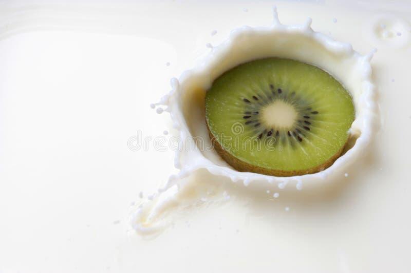 Kiwi che cade nel latte con una spruzzata fotografie stock