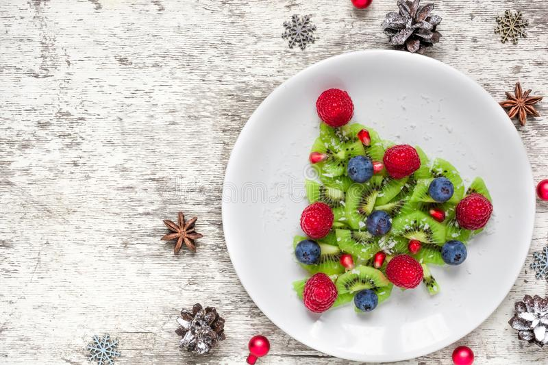 Kiwi christmas tree with berries and coconut with pine cones over white wooden table. funny food idea for kids. royalty free stock image