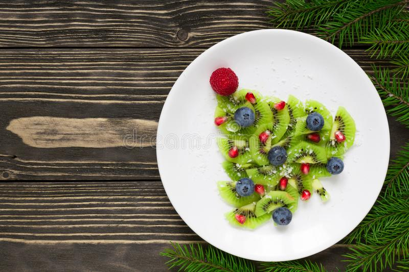 Kiwi christmas tree with fir tree branches over rustic wooden table. funny food idea for kids stock photo