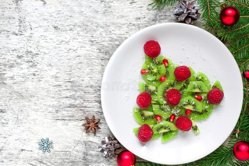 Kiwi christmas tree with raspberries, pomegranate and coconut with pine cones. funny food idea for kids royalty free stock image