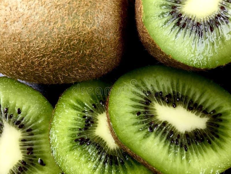 Kiwi. Close up of green kiwi halves and slices stock image