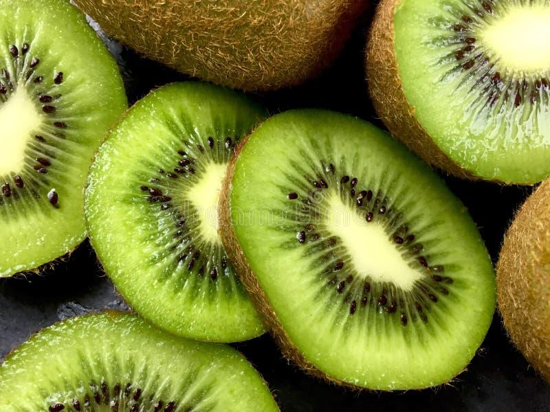 Kiwi. Close up of green kiwi halves and slices stock photography