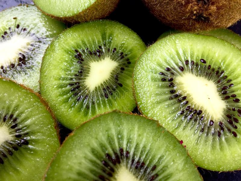 Kiwi. Close up of green kiwi halves and slices royalty free stock photos