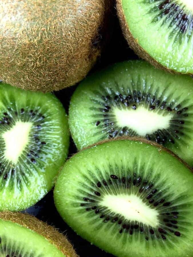 Kiwi. Close up of green kiwi halves and slices royalty free stock photo