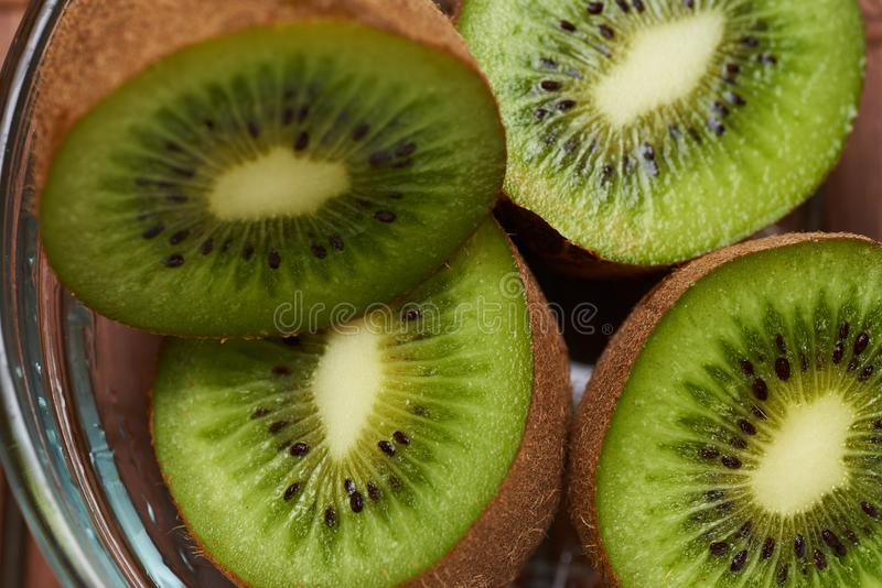 Kiwi cut in a glass plate stock photos