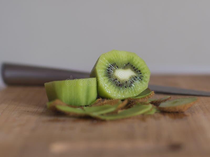 Kiwi découpé en tranches avec le couteau sur le conseil en bois photos stock