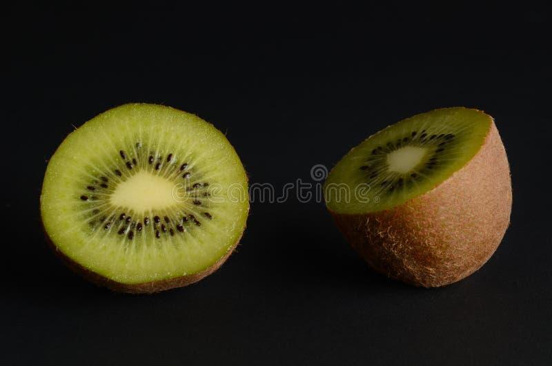 Kiwi découpé en tranches par kiwi sur le fond noir photos libres de droits