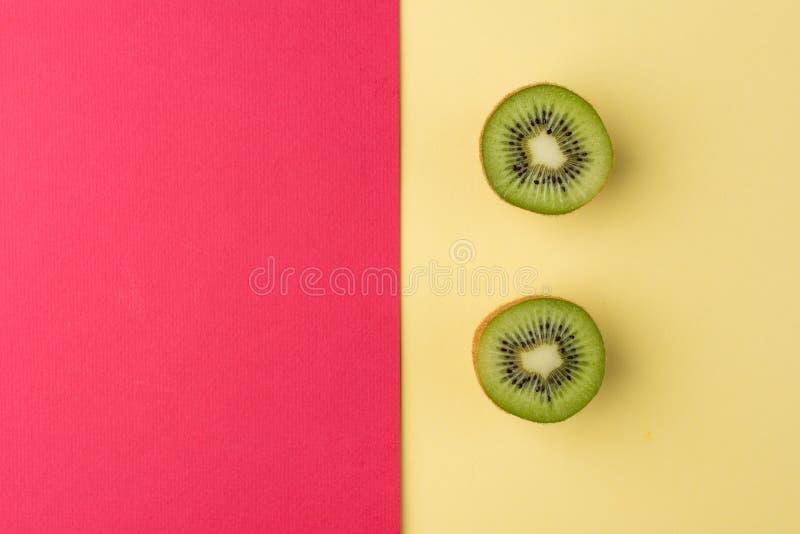 Kiwi dell'ubriaco su un fondo giallo e rosso pastello Vista superiore immagini stock