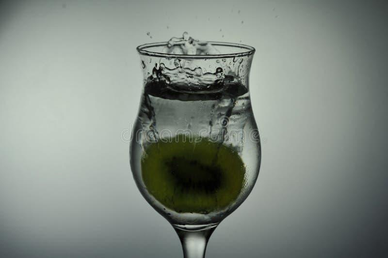 Kiwi drop in water splash royalty free stock photography