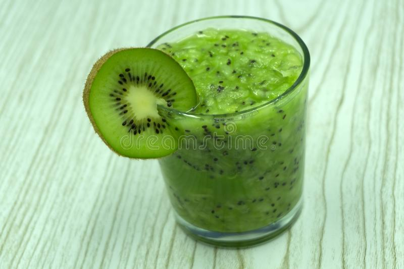 Kiwi Envy gin cocktail with sliced kiwi and ice in a glass, Mixology, refreshing cocktail, side view . royalty free stock photography