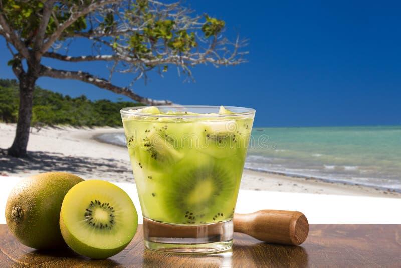 Kiwi Fruit Caipirinha av Brasilien över härlig strandbakgrund royaltyfri bild