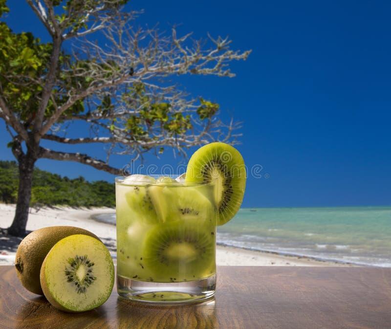 Kiwi Fruit Caipirinha av Brasilien över härlig strandbakgrund royaltyfria bilder