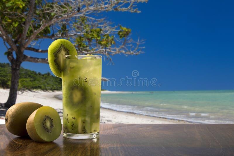 Kiwi Fruit Caipirinha av Brasilien över härlig strandbakgrund arkivbilder