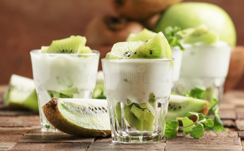Kiwi fruit with creamy yogurt dessert in glass, old wooden kitchen table background, selective focus stock photography