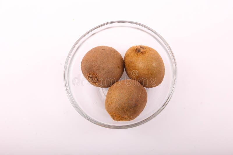 Kiwi fruit on dish. Kiwi fruit with kiwi slices on a white background royalty free stock images
