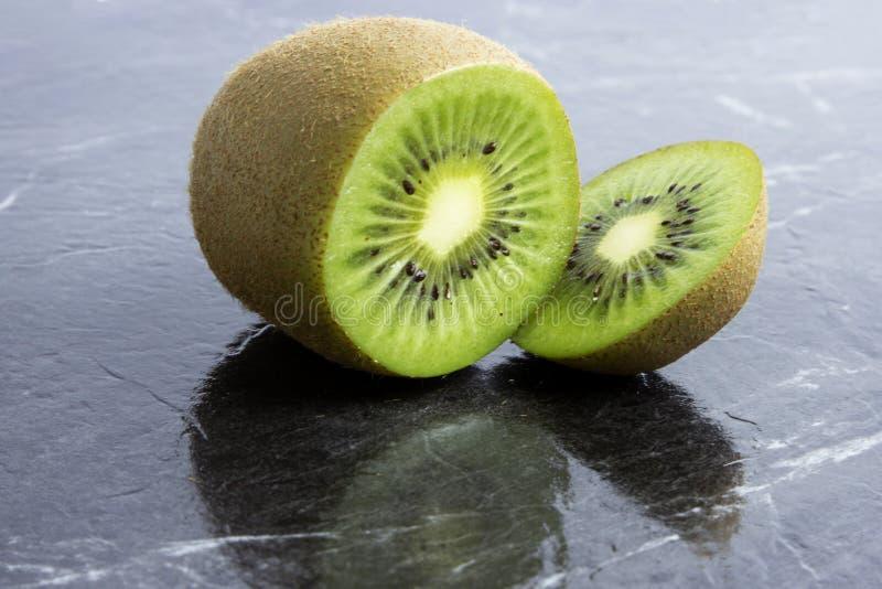Kiwi Fruit. Fresh kiwi fruit cut on black slat royalty free stock photography