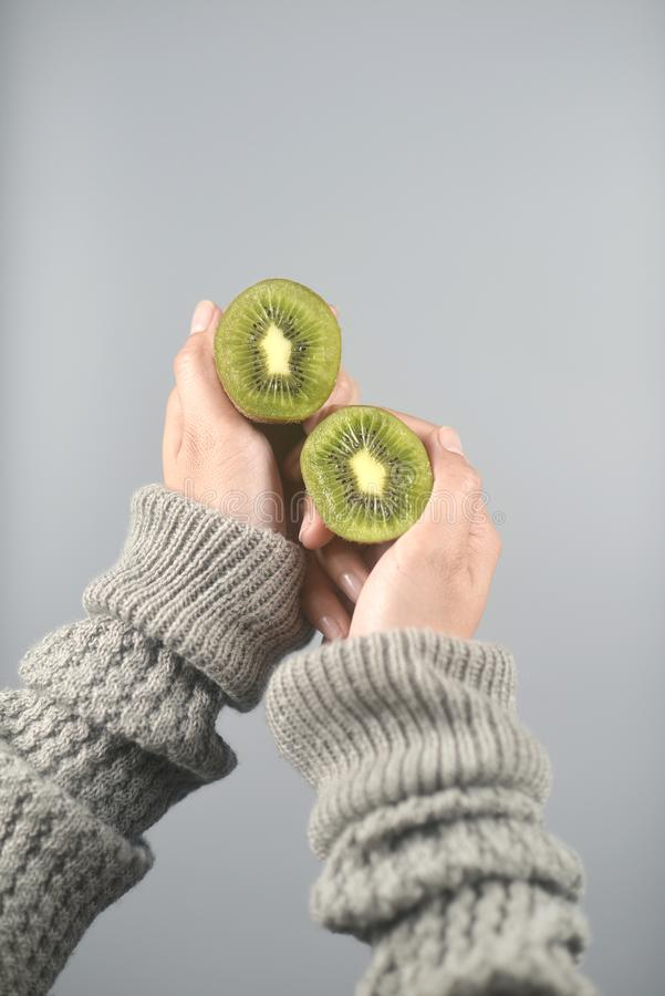 Kiwi fruit, half cut 2 pieces on women hands with sweater on light grey background. vertical image. Beautiful, brown, closeup, color, concept, design, dessert stock photography