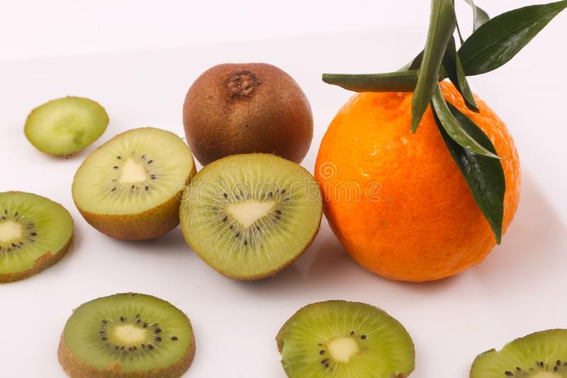 Kiwi and Tangerine fruit. Kiwi fruit with kiwi slices and tangerine on white background royalty free stock image