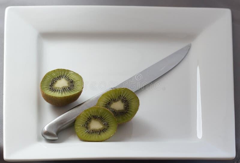 Kiwi fruit on a plate. Kiwi fruit cut and plated with a knife stock photos