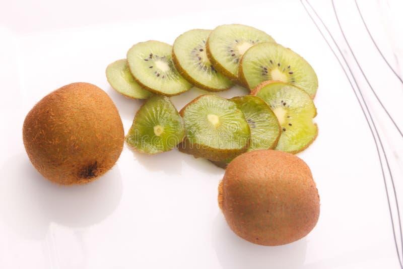 Kiwi fruit on white. Kiwi fruit with kiwi slices on a white background stock images