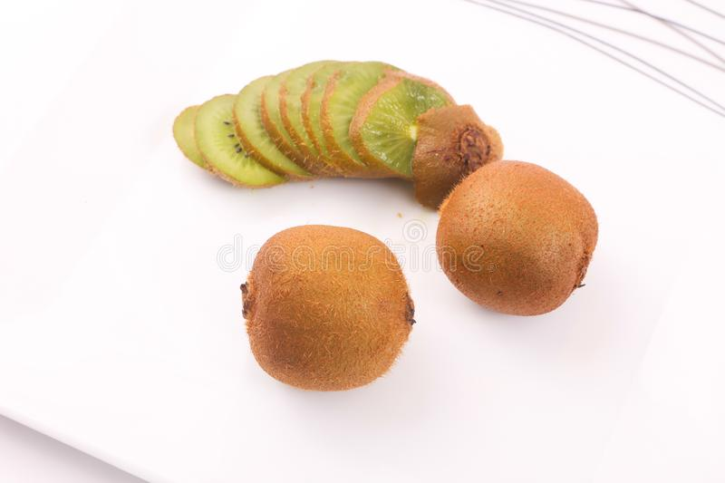 Kiwi fruit on white. Kiwi fruit with kiwi slices on a white background royalty free stock photos